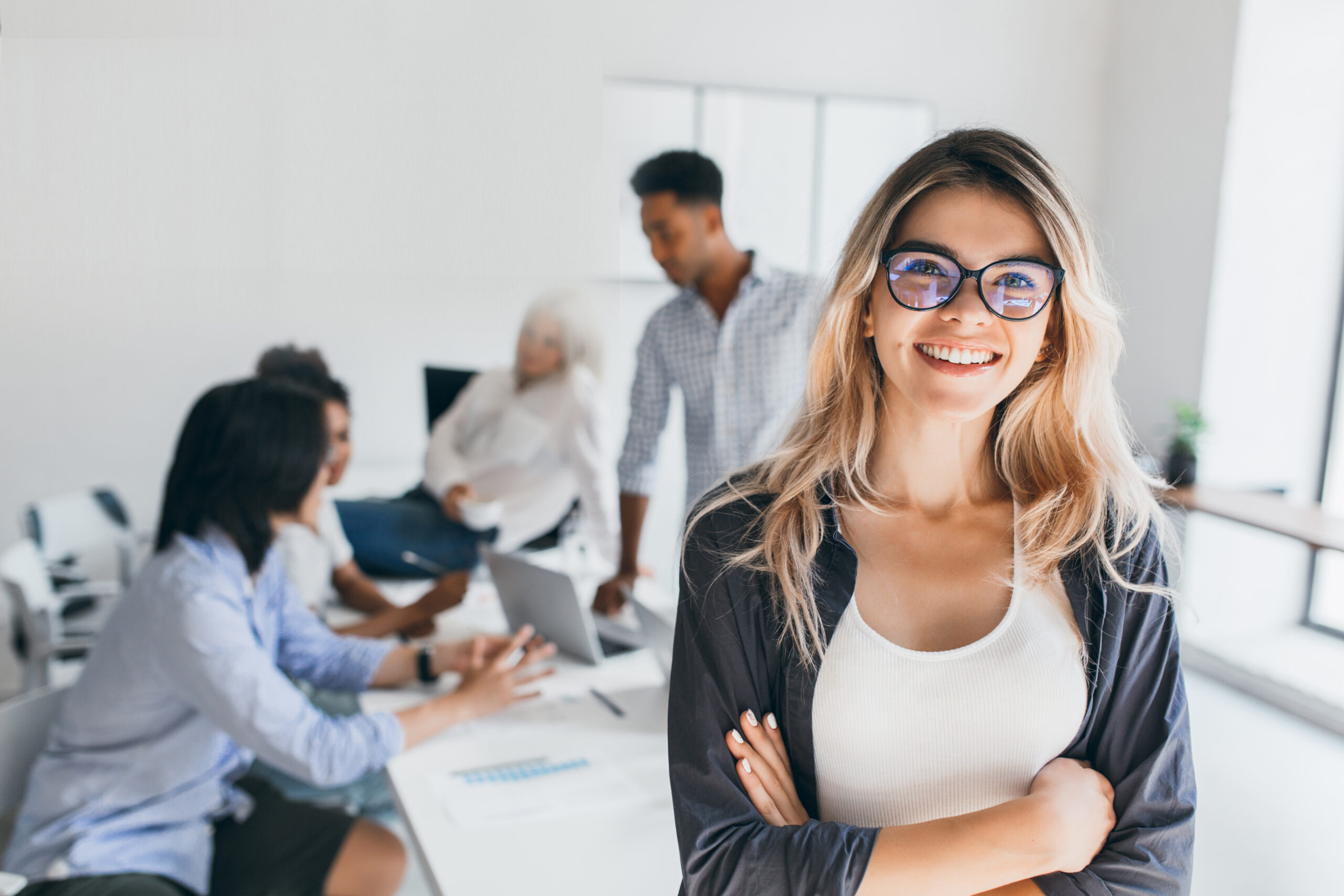 Blonde female executive posing with smile and arms crossed during brainstorm with managers. Indoor portrait of european student spending time in hall with asian and african friends.